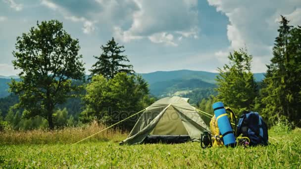 Turisztikai sátorban és két hátizsák. A hegyek és a felhők egy világos nyári napon gyönyörű zöld háttér