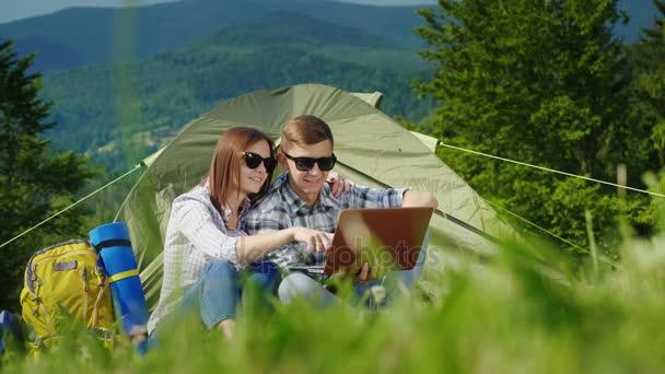 Két turisták használ laptops-ban a kemping. A festői hegyek a háttérben