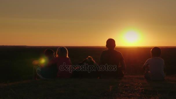 Gruppo di sagome A dei bambini con un cane sono ammirando il tramonto nella campagna. Siedono fianco a fianco, posteriore vista