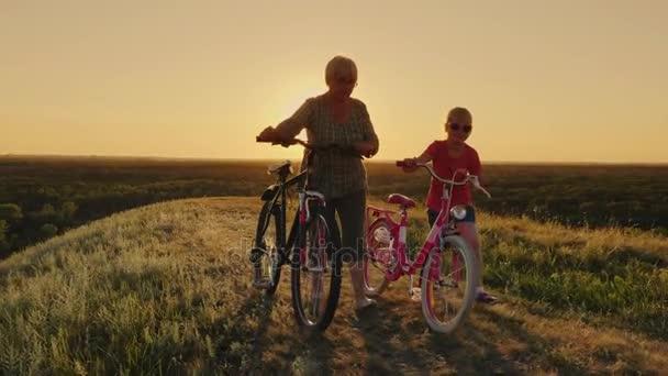 Nonna sta camminando con sua nipote. Stanno camminando a fianco, biciclette di guida. Un stile di vita sano e attive persone anziane