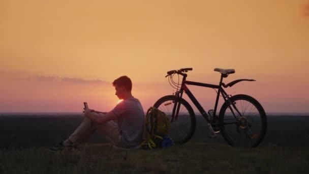Teenager používá smartphone venku. Sedí mu kolo a batoh. Při západu slunce