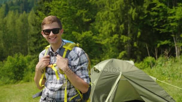 Portrét mladé Turistický batoh. Se dívá na kamery, objeví palec v gestu schválení