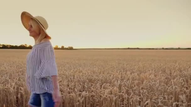 A young woman in a hat is enjoying a stroll through the wheat field, happily goes forward, smiles. Steadicam shot