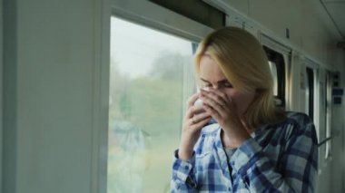 A woman with a cup of coffee looks out the window from a train. Love to travel