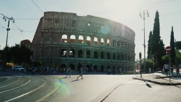 Řím, Itálie, červen 2017: Provoz vozidel a chodců v Římě na pozadí slavné Koloseum. V zářivé paprsky zapadajícího slunce