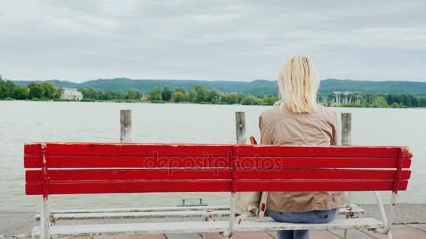 Egy nő ül egy piros pad, a tóra nyíló kilátásban gyönyörködnek. Vissza a véleményt. Pihenés a Balatonon