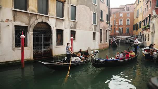 Venice, Italy, June 2017: Gondolas with tourists sail through the narrow canals of Venice. Tourism in Italy