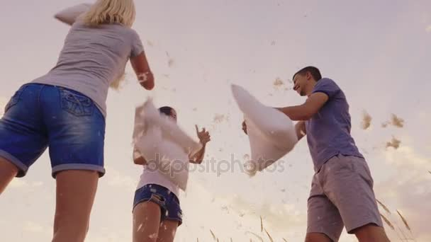 Pillow fight. A group of friends have fun - beats each other with pillows, feathers fly