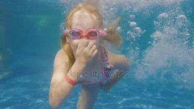Caucasian girl 6 years old learns to dive in the pool. Underwater video
