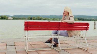 Egy nő beszél a telefonon. Ül egy piros pad, a háttérben a festői Balaton Magyarország