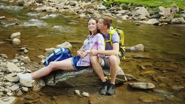 Turista hátizsákok-val egy szerető pár nyugszik, egy festői helyen, egy hegyi patak mellett. Ölelés, és egy rock ül. Kellemes Ünnepeket