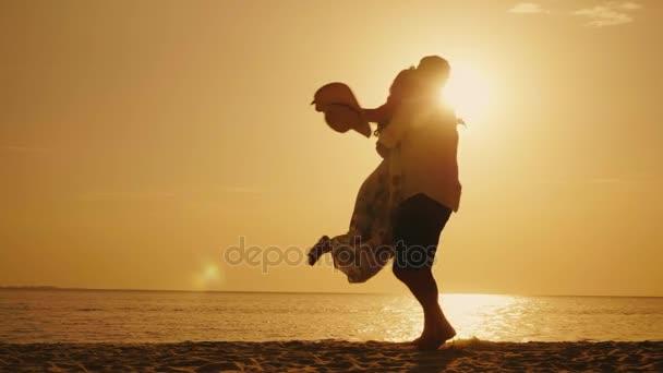 Muž je krouží ženu v náručí na pozadí moře a západ slunce. Po příjezdu na příjemnou dovolenou společně