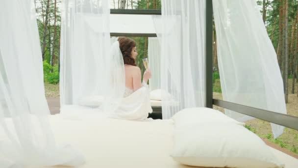 Nevěsta se sklenkou šampaňského sedí na lehátku u bazénu.