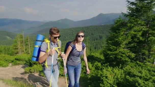 Egy fiatal pár, a hegyi ösvényen sétál. A festői hátteret a hegyek és erdők
