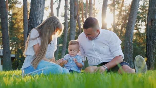 Portrét mladé šťastné rodiny. Máma, táta a dítě chlapce, který seděl na trávníku poblíž jeho domu při západu slunce