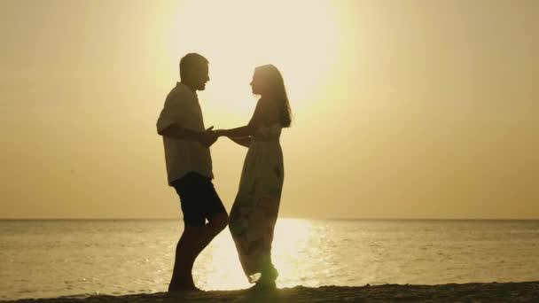 Srandovní mladý manželský pár tance na pláži. Siluety při západu slunce