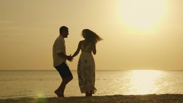 Siluety mladého páru, vtipný tanec na pozadí moře a zapadající slunce. Veselý dovolená u moře