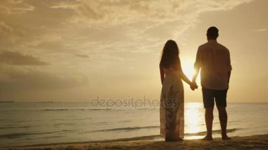 Young married couple holding hands, facing the sea and sunset. Happy Honeymoon
