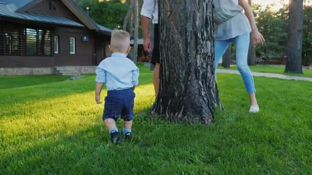 Happy parents play hide and seek with a baby boy. He runs happily behind them around the tree. Happy time with parents