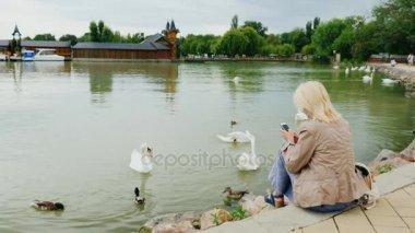 Egy fiatal nő ül a tó hattyúk. Használja a smartphone