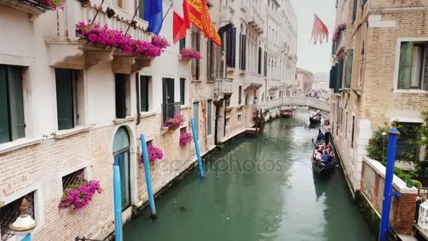 Velence, Olaszország, 2017. június: Gondolák a turisták úszni egy keskeny csatorna Velence központjába. A hagyományos építészet, Velence