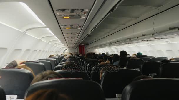 Uvnitř dopravní letoun v letu pohled zezadu. Řady sedadel s cestujícími