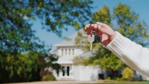 Egy kéz egy kulcstartó, az alakja egy kis házat, és a gombok. A háttérben egy tipikus ház külvárosi amerikai stílusban