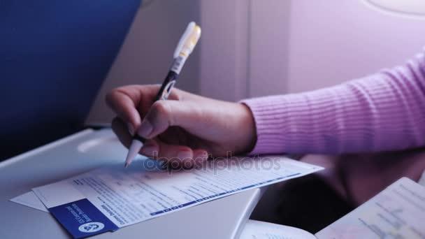 New York, USA, September 2017: Eine Person füllt ein Einwanderungsformular aus, um in die Vereinigten Staaten einzureisen. im Rahmen, nur die Hände sind sichtbar, die Person fliegt an Bord eines Flugzeugs