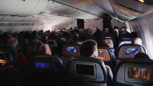 V kabině velké dopravní letadlo. Cestující v pohodlných křeslech sledovat zábavné programy na obrazovkách