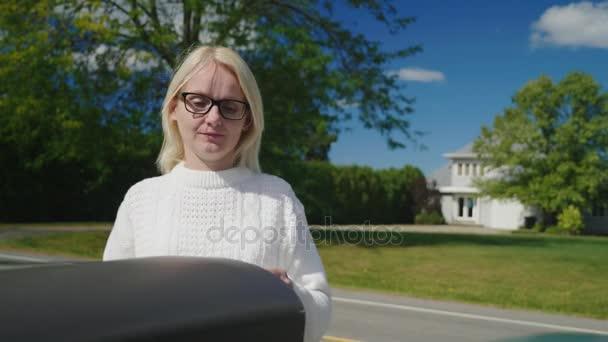Eine Frau legt die Briefe in den Briefkasten und holt eine rote Fahne für den Postboten. Einfach mailen