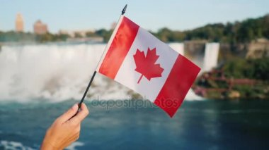 A female hand holds a Canadian flag against the background of Niagara Falls. Tourism in Canada