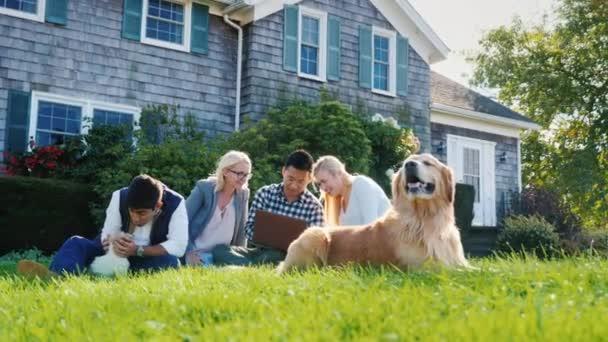 Mnohonárodnostní skupiny přátel odpočívá ve dvoře domu. Sedí na trávě, hrát se psem, Užijte si laptop