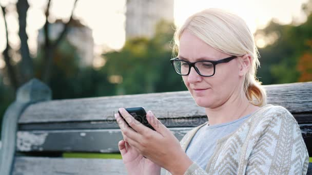 A young woman in glasses is using a smartphone. Sits on a park bench