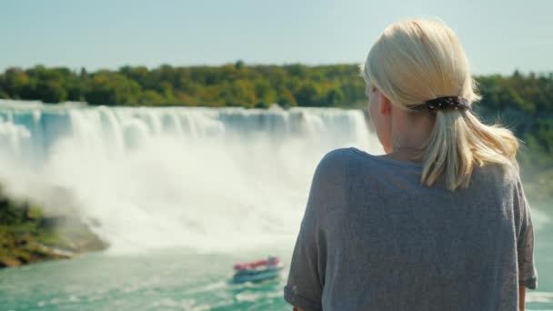 Eine junge Frau bewundert die Niagara-Fälle. Hinten Sie Ansicht von. Tourismus in den Usa und Kanada Konzept