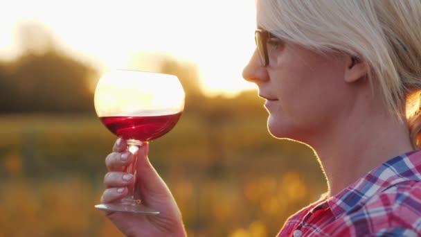 eine Frau verkostet Rotwein. bei Sonnenuntergang mit einem Glas neben dem Weinberg stehen