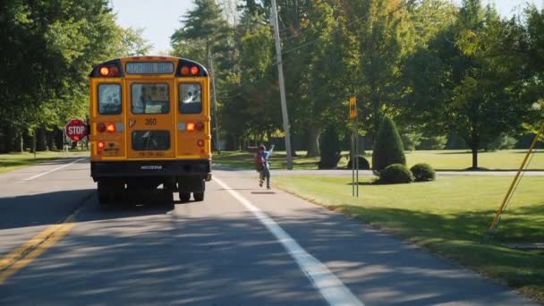 Lockport, NY, USA, October 2017: A little boy comes out of the yellow school bus. Cars pass it, it safely crosses the road. Safety on the road concept