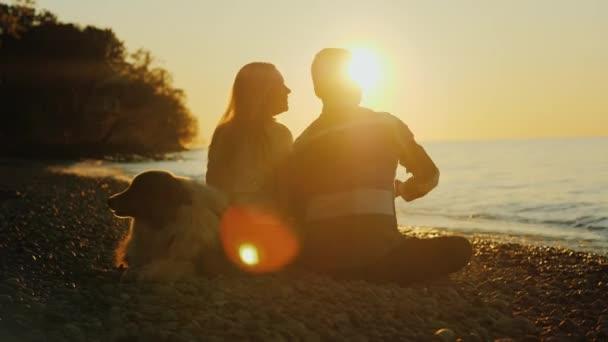Siluety mladé romantický pár se psem. Sedí na okraji vody. Číňan a běloška