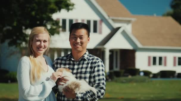 Portrét mladého multietnické páru s štěně v rukou. Podívejte se na fotoaparát, postavte před svůj dům