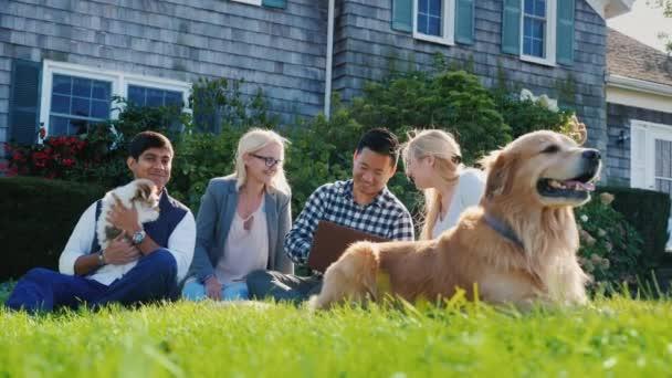 Skupina přátel relaxaci na zahradě, hrát se psy, na přenosném počítači