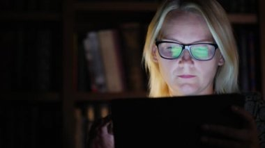 Young woman in glasses works with a tablet in the office late at night. Working extra hours