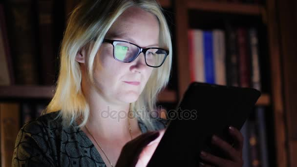 Žena pracuje s tabletem v knihovně pozdě v noci. Práce až do pozdních hodin