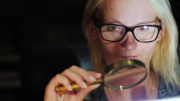A woman looks at something through a magnifying glass