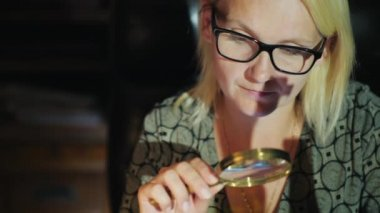 A woman in glasses looks at something through a magnifying glass. Careful study