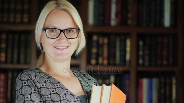 Portrét ženy v knihovně. Ona drží knihy, při pohledu na fotoaparát. Na pozadí polic s knihami