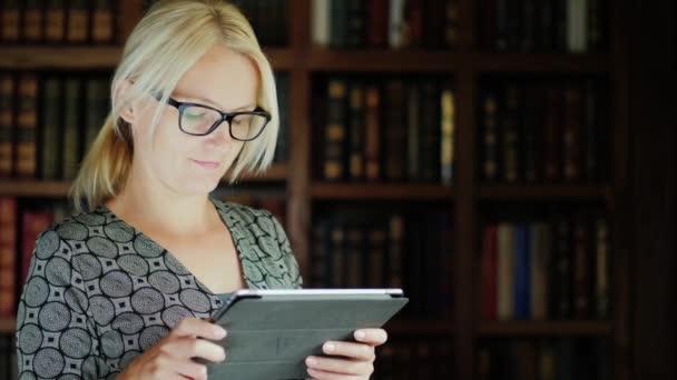 Hezká žena v brýlích používá tablet v knihovně. Stojící na pozadí polic s knihami