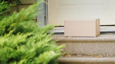 The woman takes the parcel from the threshold of her house. In the frame, only the door, the box and the legs of the woman are visible