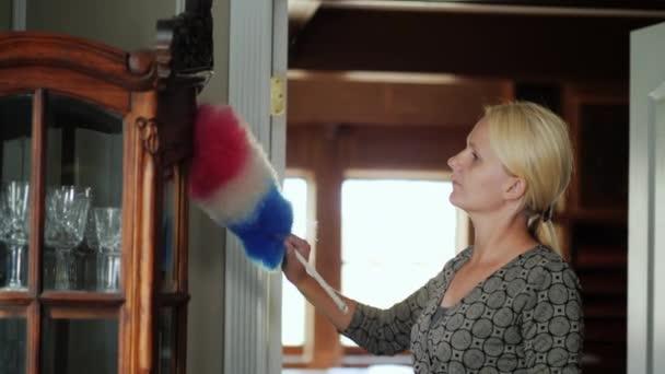 Žena myje prach z příborníku nádobí. Úklid domu