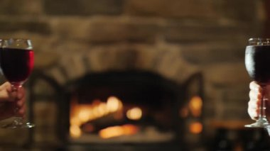 Clinking glasses on the background of a burning fireplace. Slow motion video