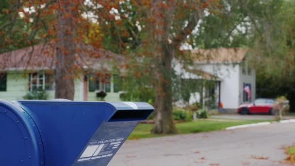 Eine Frau mit einem Hund im Arm nähert sich eine Mail-Box auf der Straße und wirft einen Brief hinein