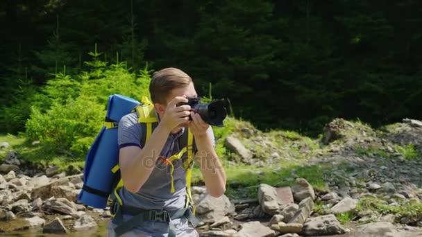 A hátizsák egy turisztikai lelkesen képei tájak. Festői helyen, egy hegyi folyó, a háttérben egy erdő közelében. Pihenés és az aktív életmód fogalma